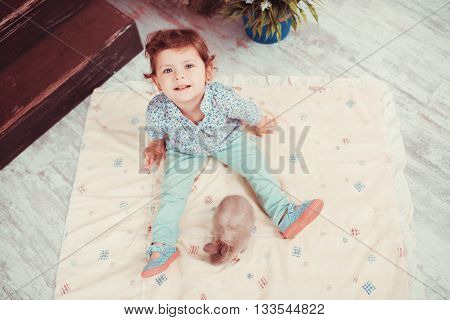 The Little Red-haired Girl Playing With Rabbit In The Room. The Concept Of Happiness, Joy And Family