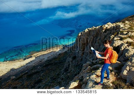 female traveler with backpack and map standing on the cliff against sea and blue sky at early morning