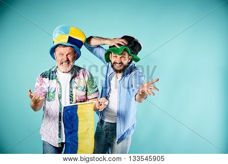 The two football fans with a flag of Ukraine over blue background