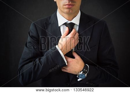 Man fixing his tie with both hands