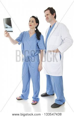 Two medical personnel looking pleased as they check a patient's food X-ray together. Isolated on white.