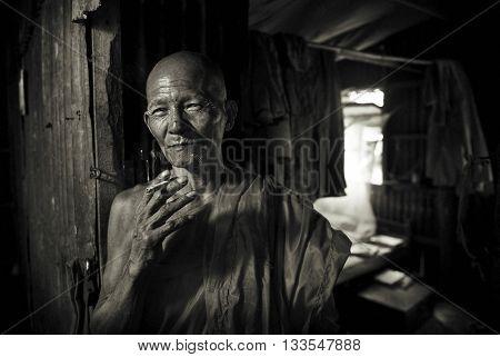 Smoking Cambodian Monk Portrait Concept
