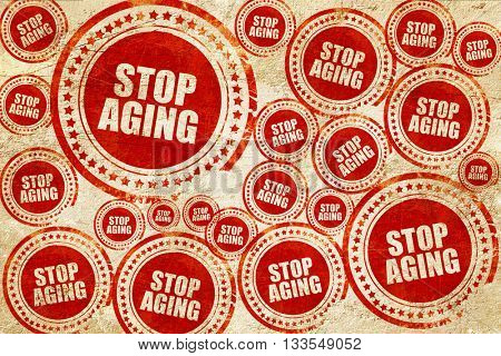 stop aging, red stamp on a grunge paper texture