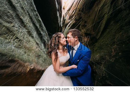 Happy newlyweds kissing at weathered dark rock cleft.