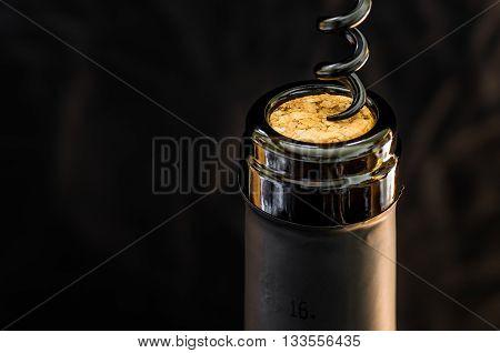 Opening a bottle of wine corkscrew closeup