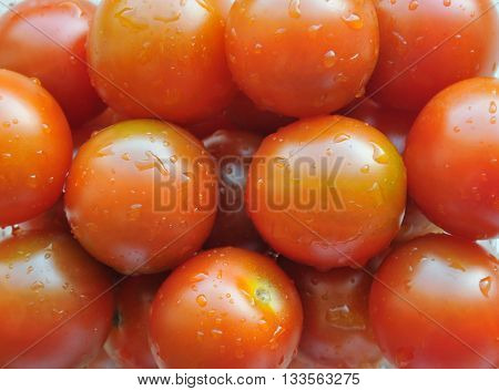 Multitude of juicy cherry tomatoes closeup, background