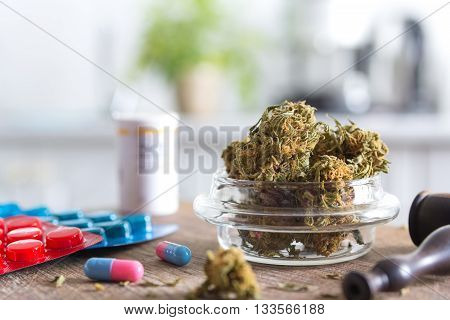 Marijuana buds in the glass plate on the wooden board and medications. Medical marijuana concept
