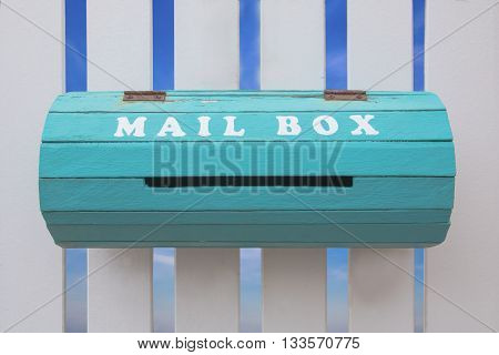 A vintage mailbox with white wall background