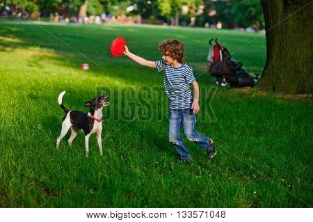 The little fellow trains a dog in park. He holds a red disk in hand. The dog has opened a mouth and has flicked out tongue language. She was tired.
