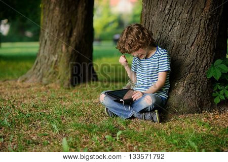 The boy is keen on game on the tablet. He has raised a hand with the clenched fist. The person is strained. Behind the back of the boy a trunk of an old tree. Jeans full of holes.