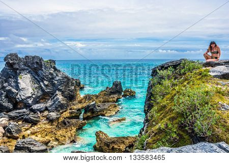 HORSESHOE BAY BERMUDA - MAY 26 - A girl enjoys the beauty of a rocky seascape in Horseshoe Bay on May 26 2016 in Bermuda.