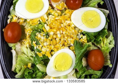 fresh green salad of lettuce egg cherry tomato and grated cheese