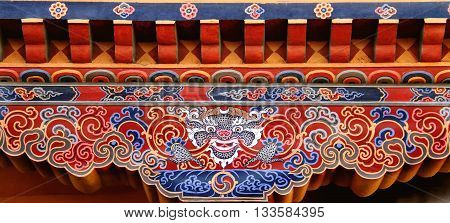 Colorful Bhutanese art of Tibetan dragon painted on wood at the entrance of house at Paro Bhutan