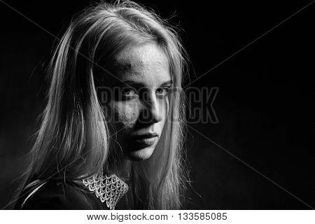 blond girl with pimply skin crying on black background monochrome
