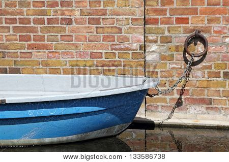 A blue rowing boat is docked at a brick wall