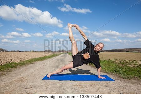 on an sunny day this man enjoys Vasisthasana or Side Plank Pose yoga in nature
