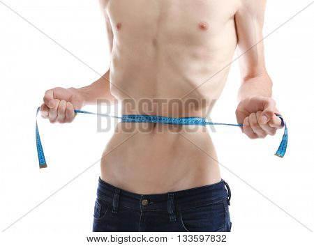 Young man measuring himself on white background