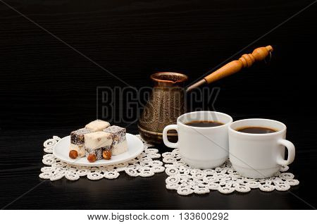 Two mugs of coffee Turkish lokum with hazelnut Cezve on a black background poster