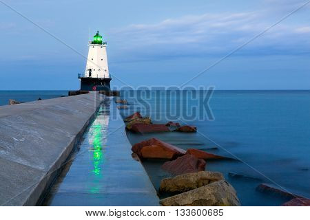Ludington Pier Lighthouse. The green beacon light of the north breakwater pier light reflects on the wet pier in the early morning blue hour light in Ludington Michigan