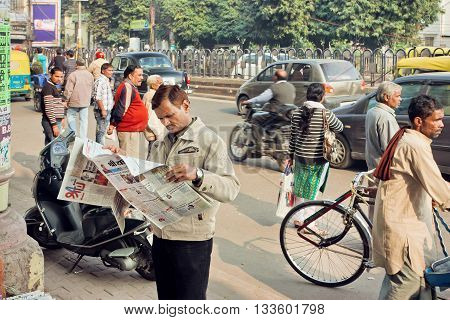 LUCKNOW, INDIA - JAN 31,: Man reading a newspaper in crowd of busy people on the street on January 31, 2016. Lucknow with population of 6000455 is largest city of Uttar Pradesh