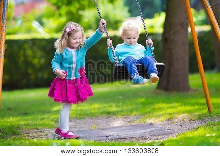 Little boy and girl on a playground. Child playing outdoors in summer. Kids play on school yard. Happy kid in kindergarten or preschool. Children having fun at daycare play ground. Toddler on a swing.