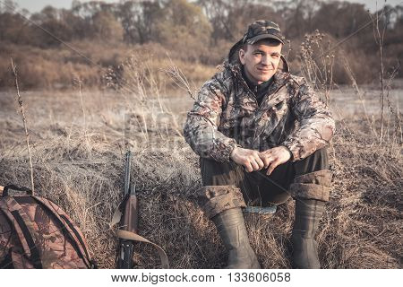 Hunter man in rural field with shotgun and backpack during hunting season