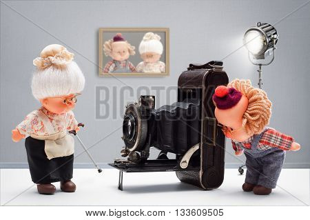Puppets of senior photographer taking with passion until the end pictures of his old ladies with vintage camera in his studio
