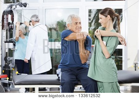 Nurse Guiding Senior Man In Stretching Exercise At Rehab Center