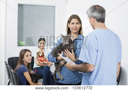 Woman Carrying Cat While Looking At Nurse In Clinic
