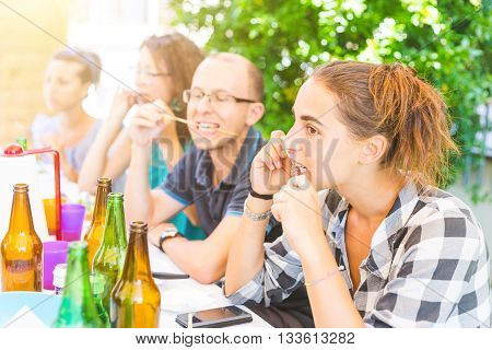 Group of friends eating meat skewers on a pic nic lunch. they are sitting next to a table having lunch and fun together.
