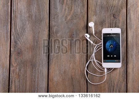 White smart phone with headphones on wooden background