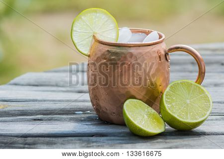 Moscow mule with limes laying to the side of hammered copper mug.
