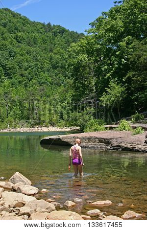 a teen-aged girl wading in a shallow mountain stream