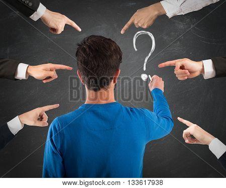 Boy writes a question mark on blackboard