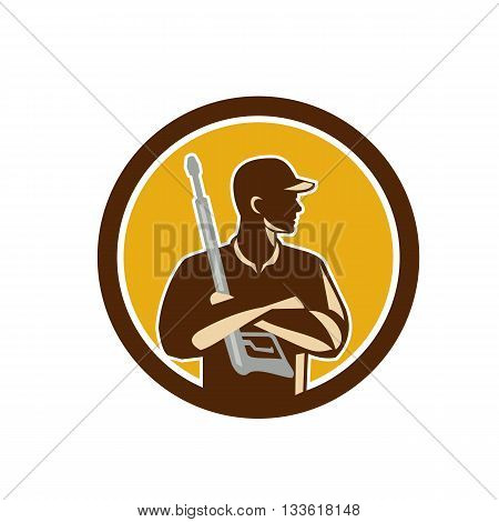 Illustration of power washer worker with arms crossed holding pressure washing gun looking to the side viewed from front set inside circle on isolated background done in retro style.