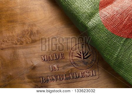 A reprint of the stamp on a wooden surface - Made in Bangladesh with the country's flag.