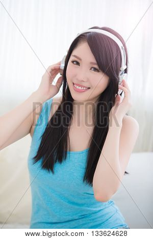 Young woman enjoying the music and relax sit at home asian beauty