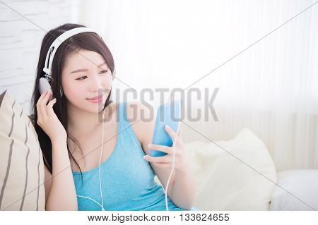 Young woman enjoying the music by smart phone and relax sit at home asian beauty