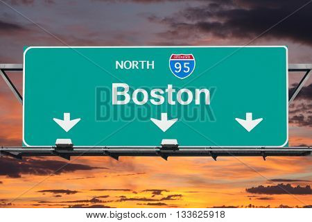 Interstate 95 north to Boston highway sign with sunrise sky.