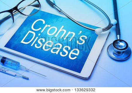 Crohn's disease word on tablet screen with medical equipment on background