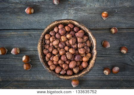 Hazelnuts in bowl on dark wooden background, top view, selective focus