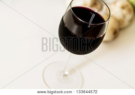 Glass of red wine Merlot on the white table