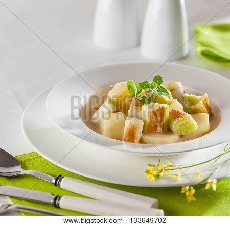 A plate of cooked potatoes with leek