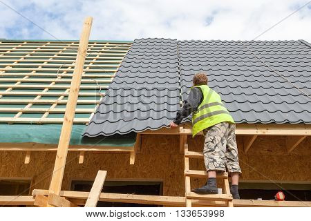 Roofer worker installing a metal tile on a new wooden house poster