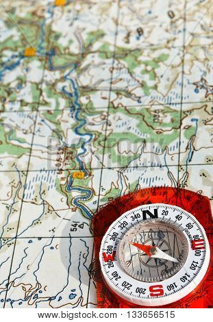 The compass on the map. Photo magnetic compass located on a topographic map.