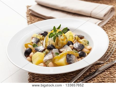 A salad with herring beans potato cauliflower and bell pepper