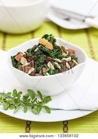 Spinach in a bowl prepared with garlic raisins bacon and pine seeds