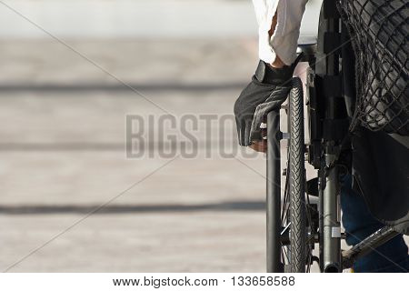 Detail of a man using a wheelchair,view from behind. Copy space on the left side