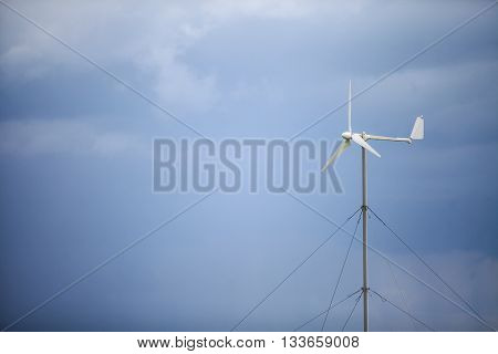 Color image of a wind vane on a cloudy day.