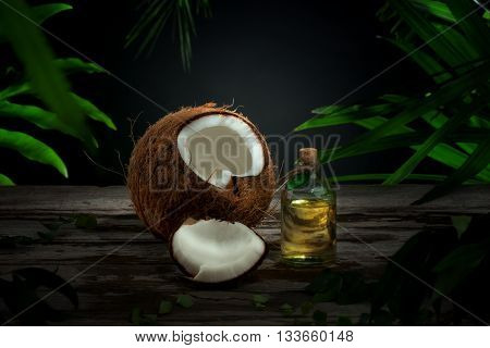 Close up view of nice fresh coconut and oil on green leaf background